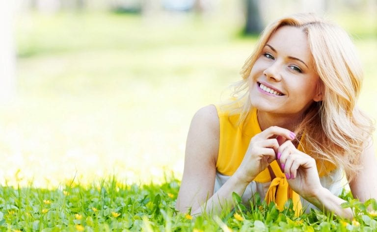 smiling woman lying on grass