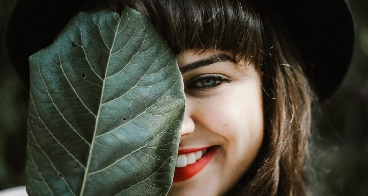 smiling woman covering nose
