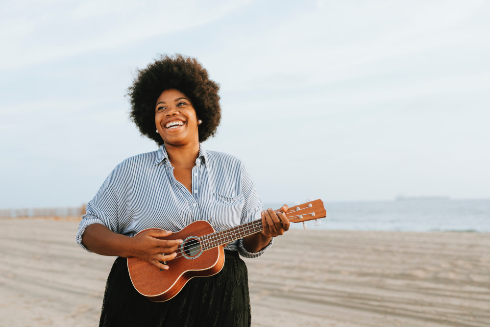 Woman playing little acoustic guitar on the beach