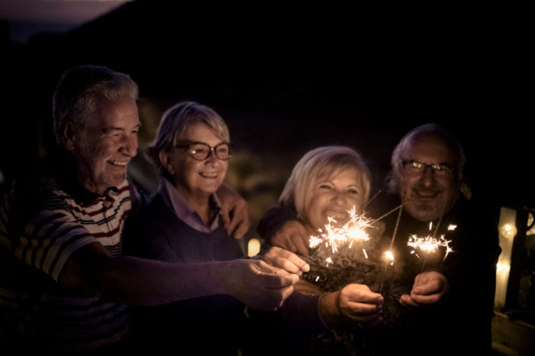 Four seniors with sparklers outside at night