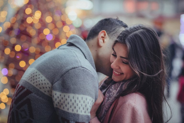 Man and woman embracing in front of holiday lights