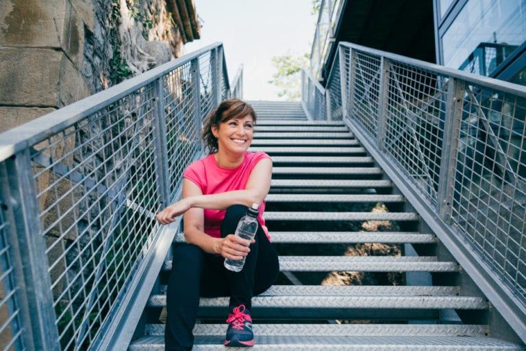 Woman in workout clothes sitting on the stairs.