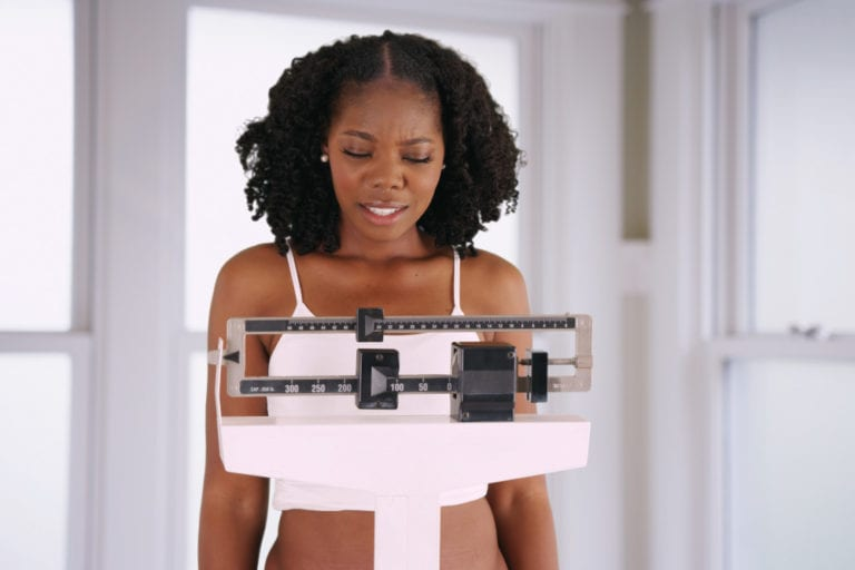 Young woman weighs herself on scale disappointed with weight gain.