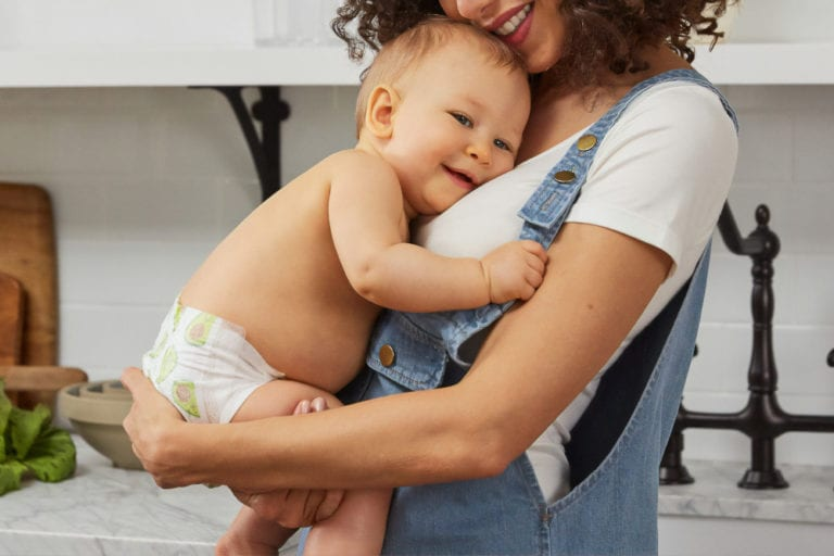 Woman wearing overalls and holding her baby.